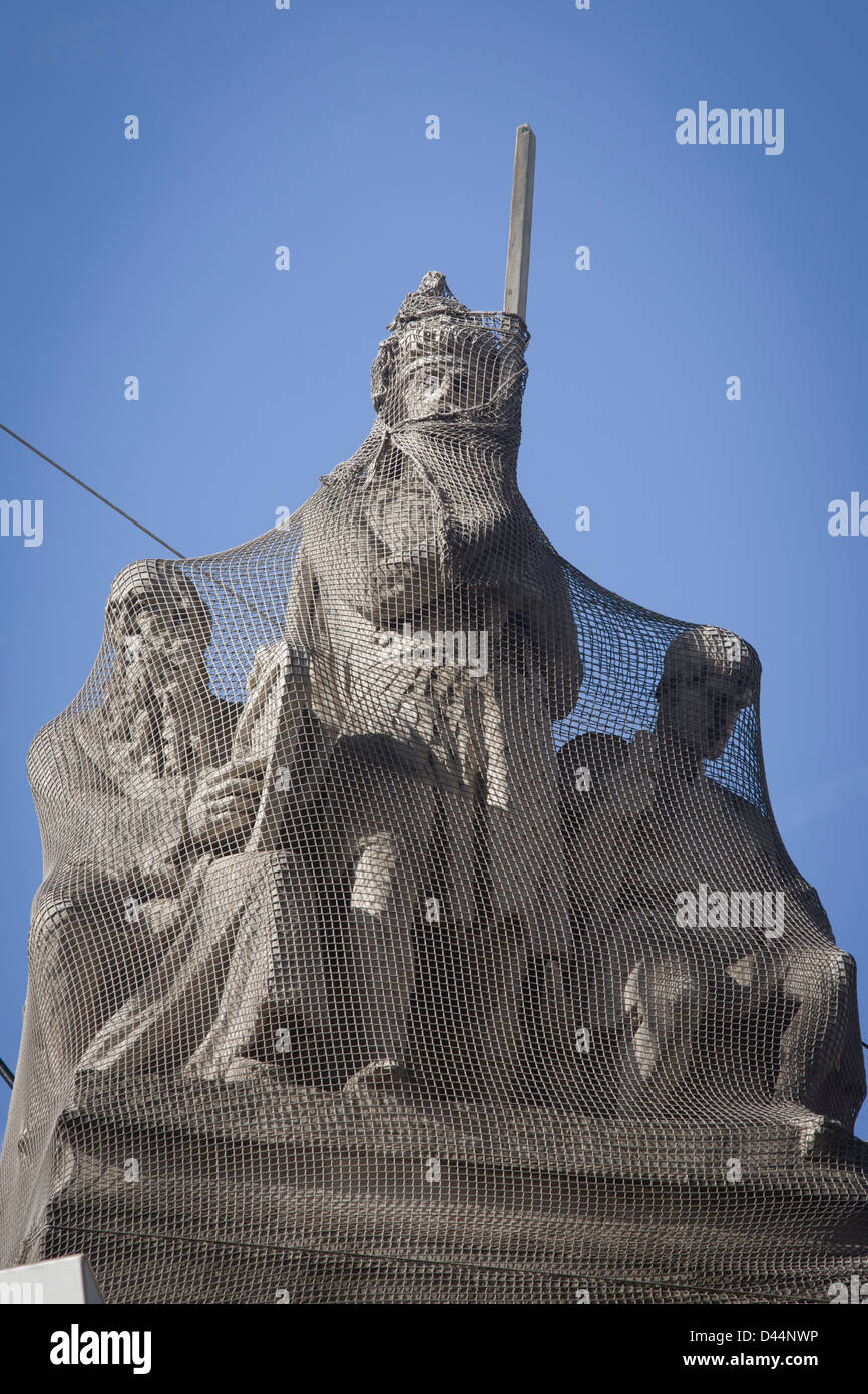 Netting protects statues from birds on the roof of Gibson Hall in the capital's Bishopgate Street in the heart - Stock Image