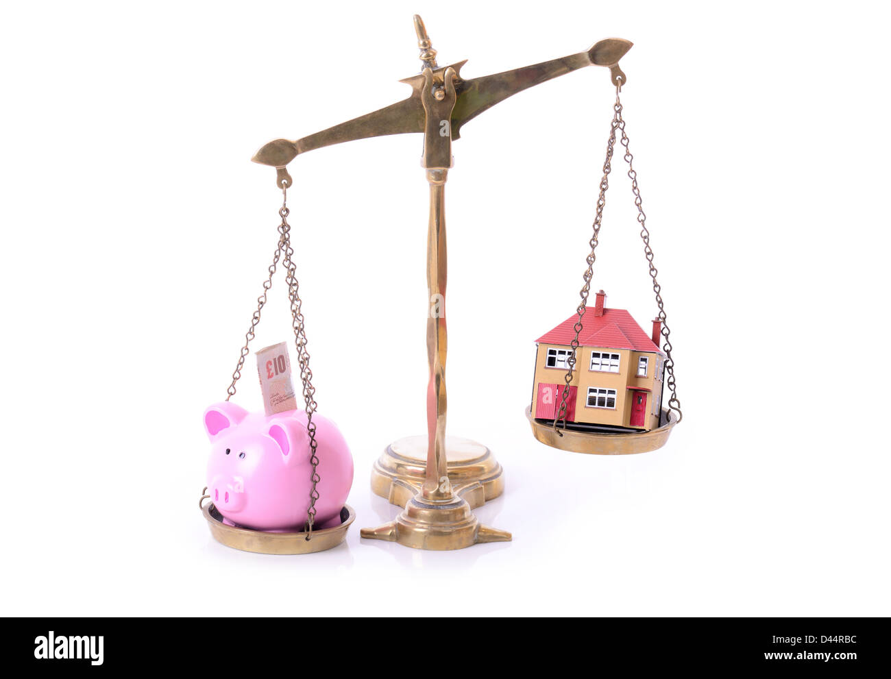concept of mortgage and saving piggy bank and house on scales - Stock Image