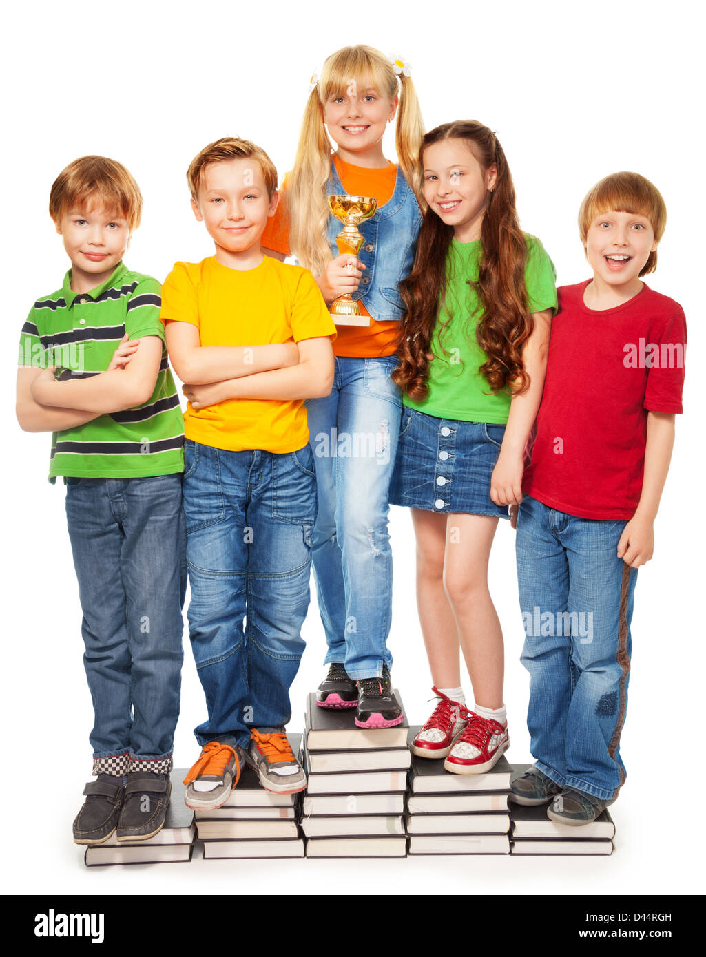 Girls and boys standing on books holding their award - Stock Image