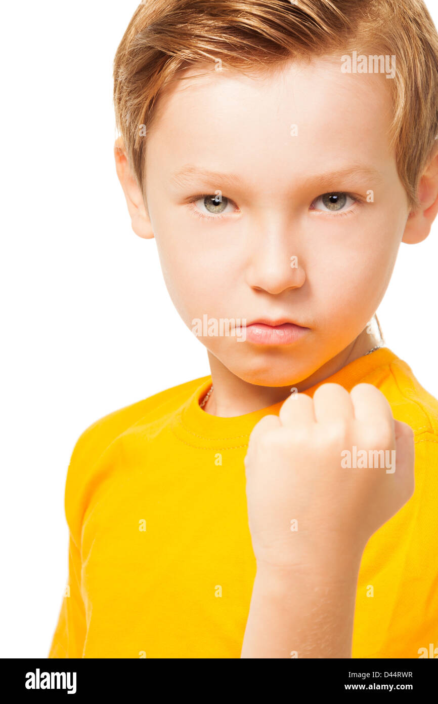 Bad tempered kid showing his fist ready to punch isolated on white Stock Photo