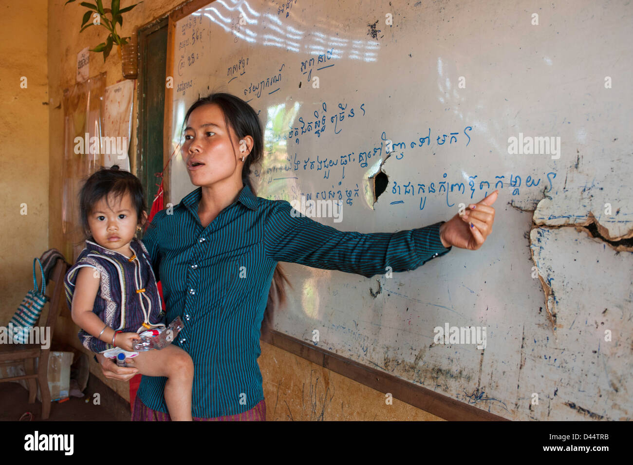 Cambodia teacher holding carrying her own child while teaching on a warped and cracked blackboard - Stock Image