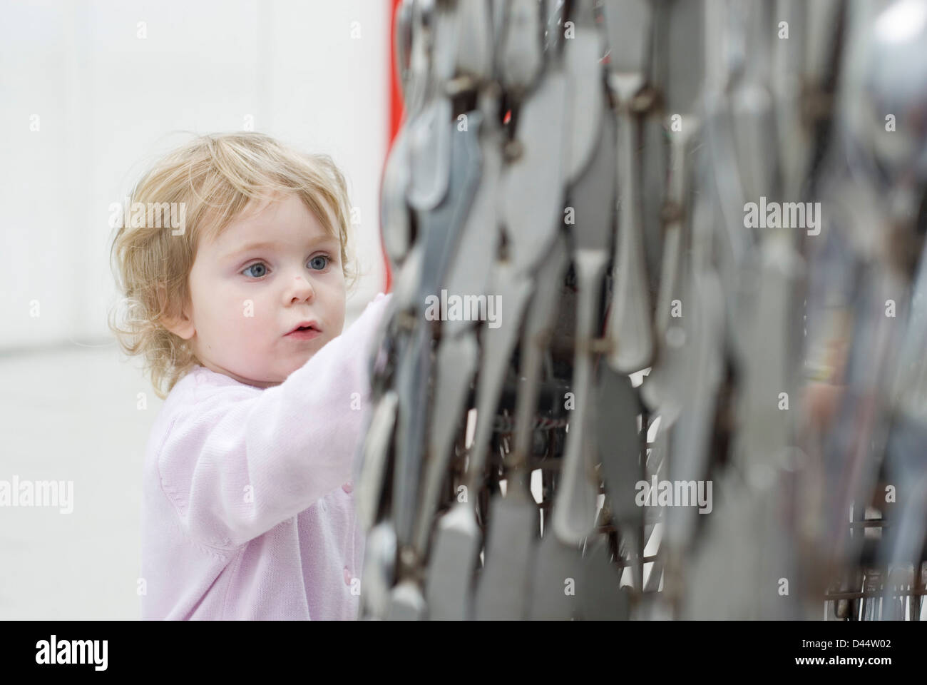 Little girl entranced by the cutlery statue, Millennium Galleries Museum, Sheffield, UK - Stock Image