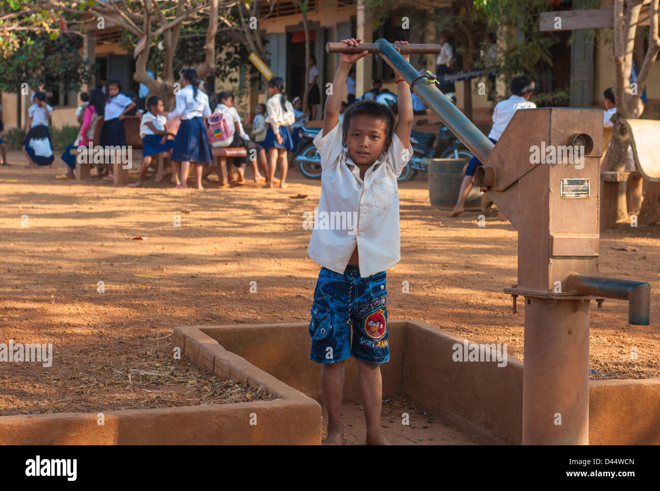 Young student pumping water at school well in cambodia - Stock Image