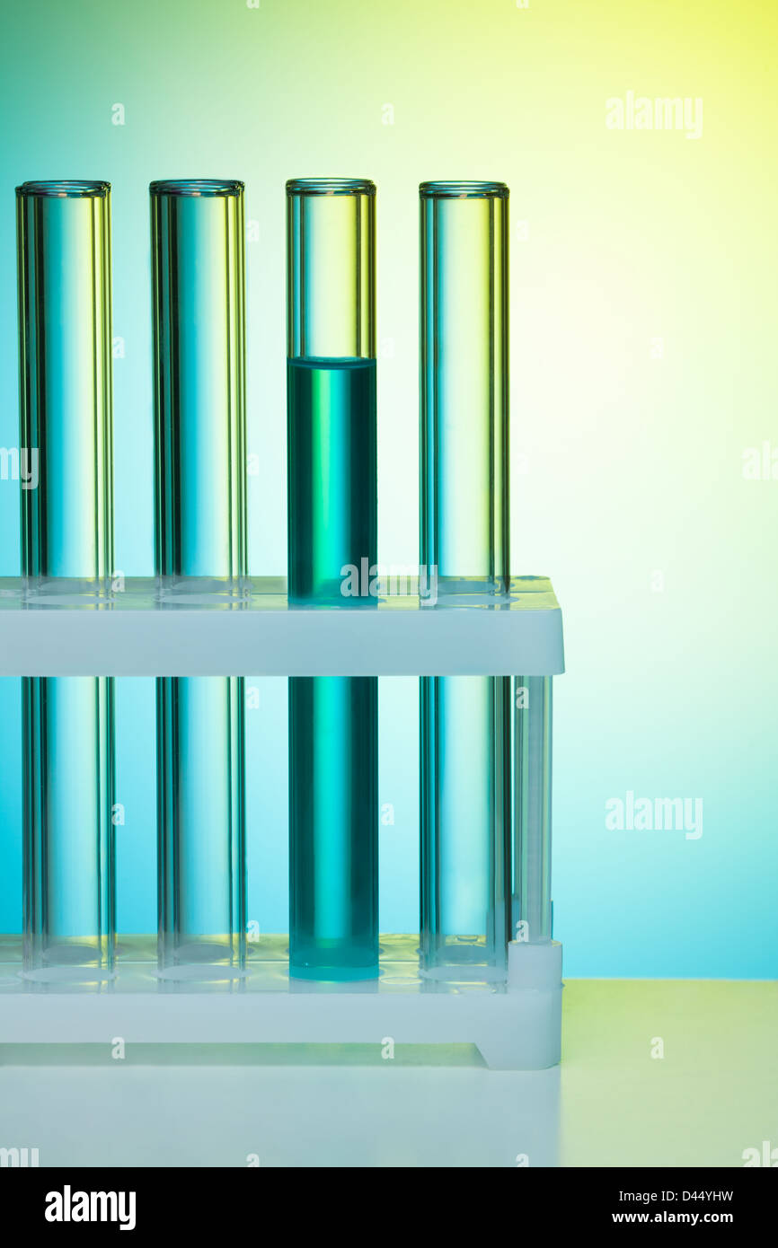 A number of test tubes on blue background in the lab - Stock Image