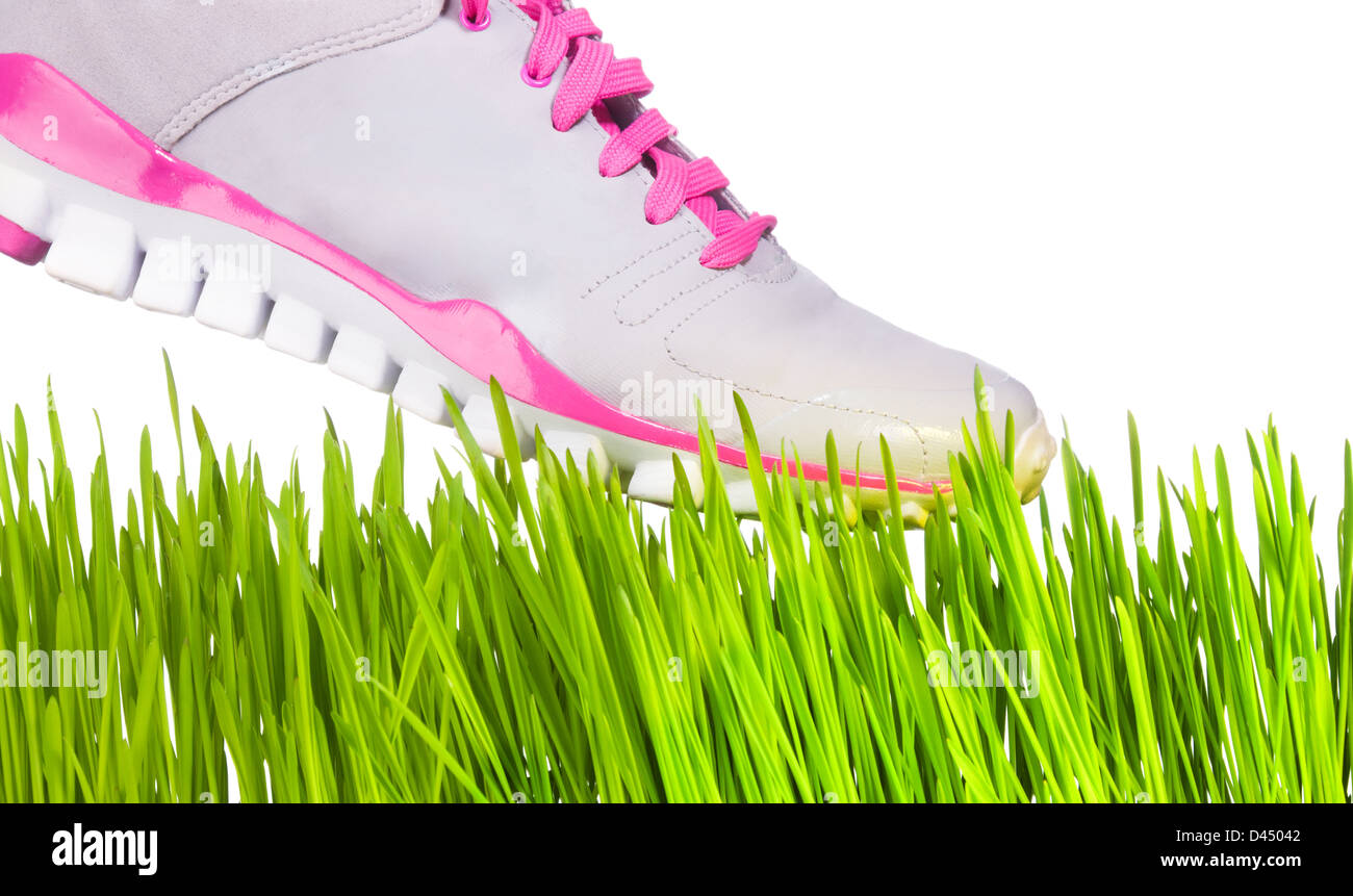 Sneaker stepping on grass - fragility concept - Stock Image