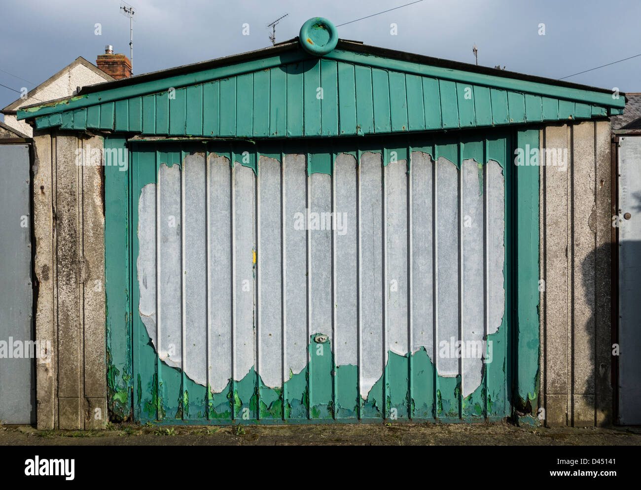A sagging and dilapidated garage door with peeling green paint - Stock Image