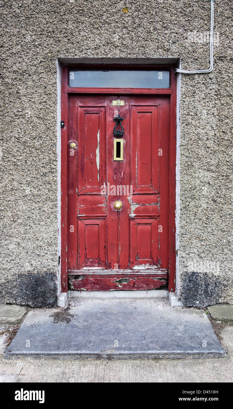 A distressed red door with peeling paint in an old house - Skerries, co.Dublin, Ireland - Stock Image