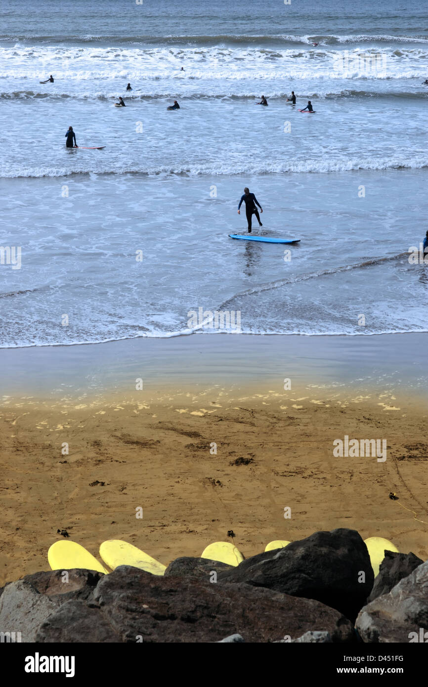 surfers wading out on the beach in lahinch county clare ireland on a beautiful day - Stock Image