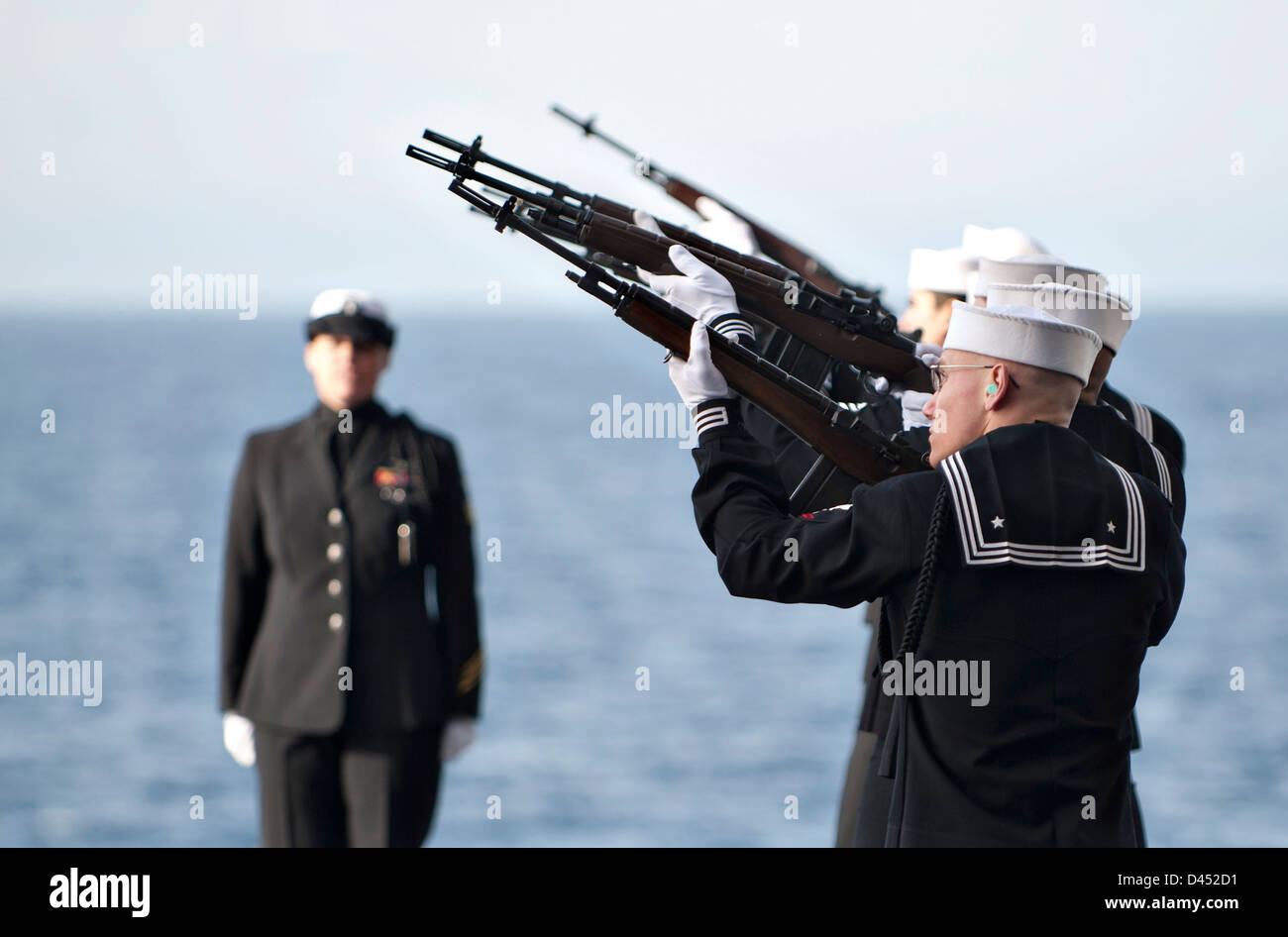 US Navy honor guard render a gun salute during a burial at sea for 20 former service members aboard the aircraft - Stock Image