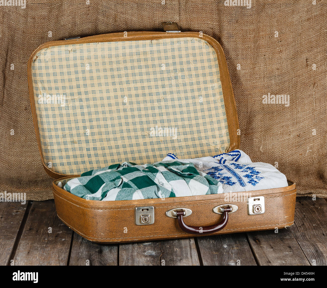 Old shabby suitcase with clothes - Stock Image