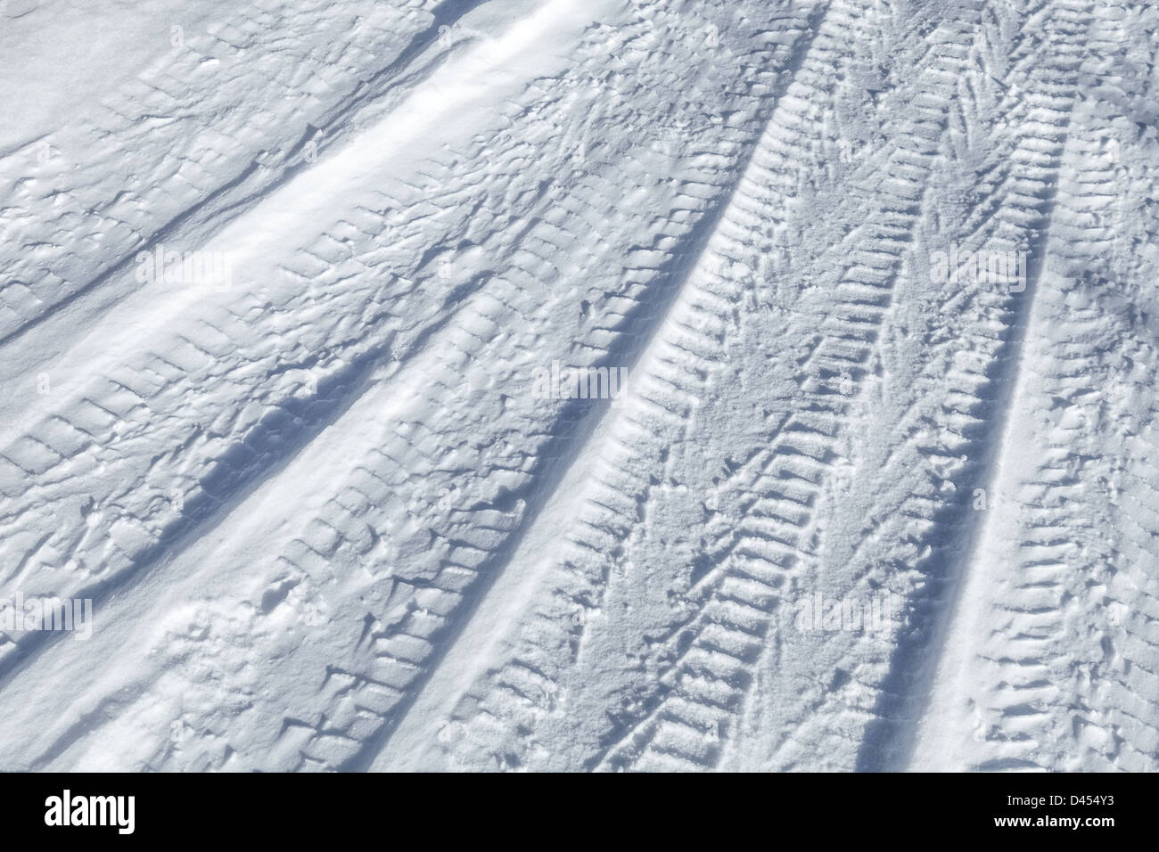 Background texture of tire tracks on road covered with snow - Stock Image