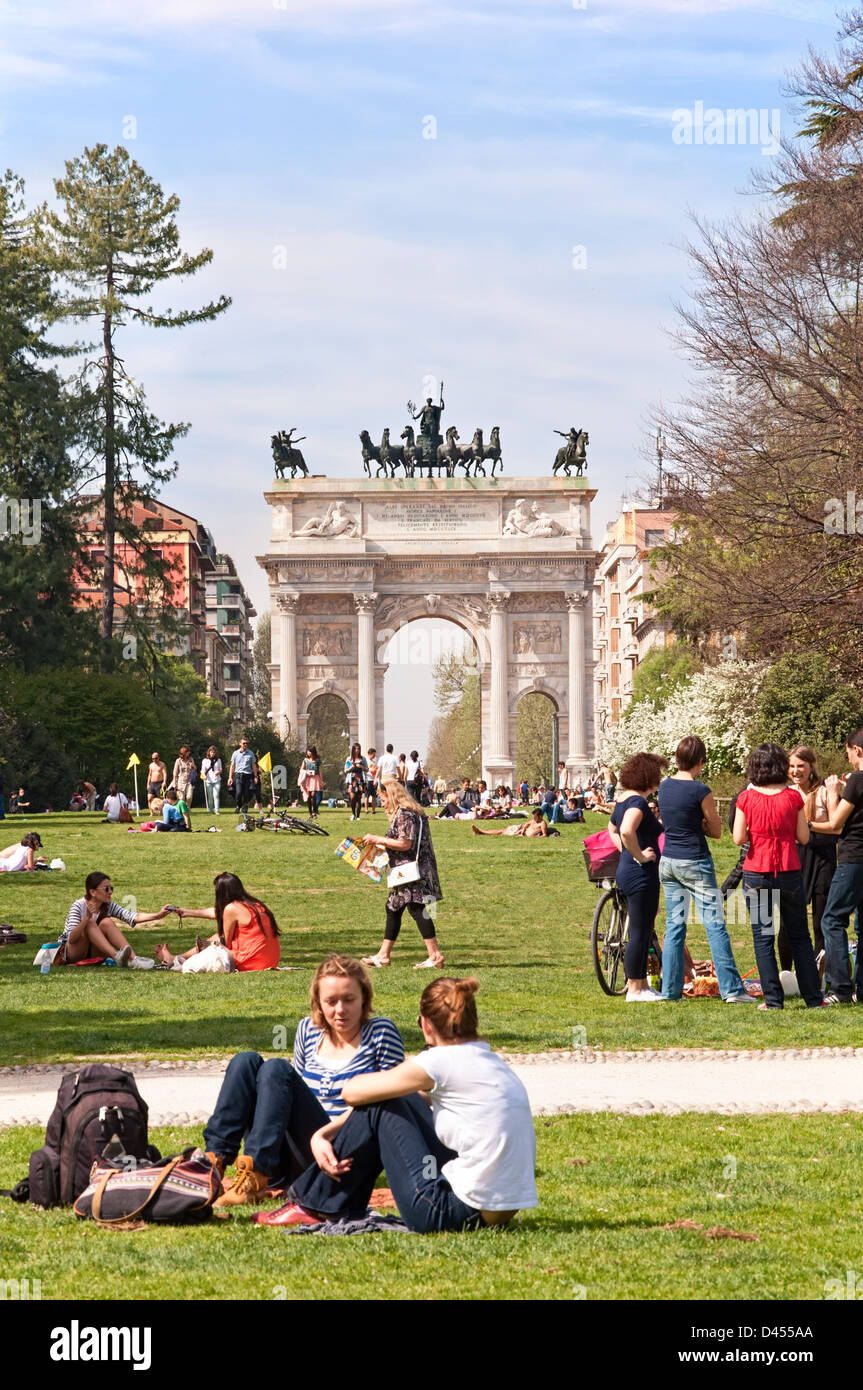 People enjoying the sunny weather at Parco Sempione with Arch of Peace in the background. - Stock Image