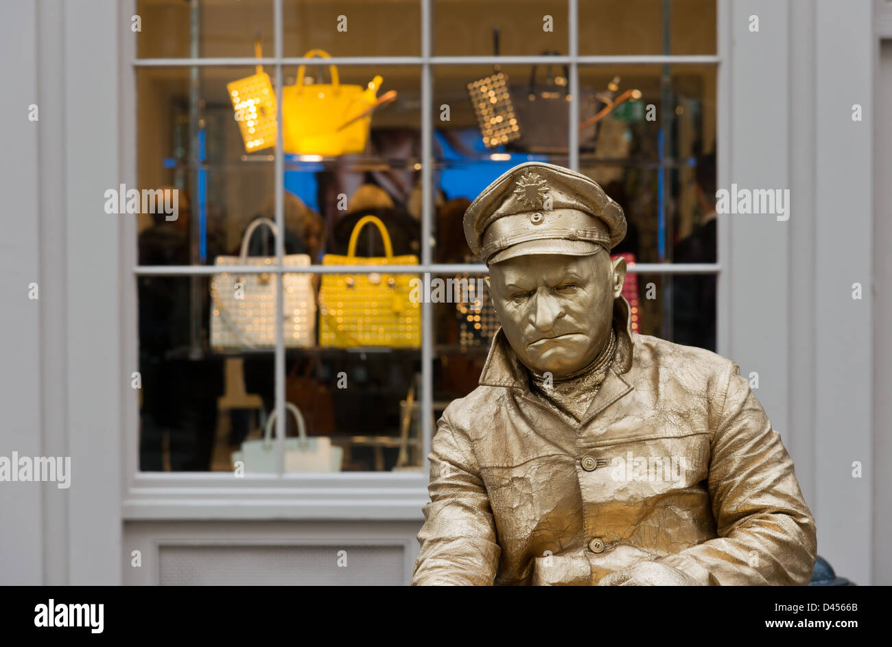 Gold painted male mime artist by a shop window Covent Garden London ...