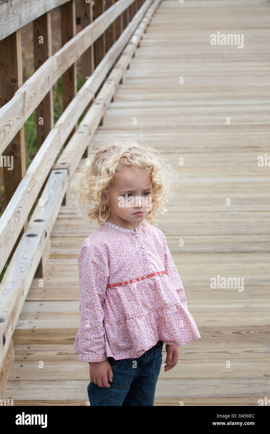 Little girl, age 3, on hiking trail, refusing to go any further. She is tired and wants to go home. - Stock Image