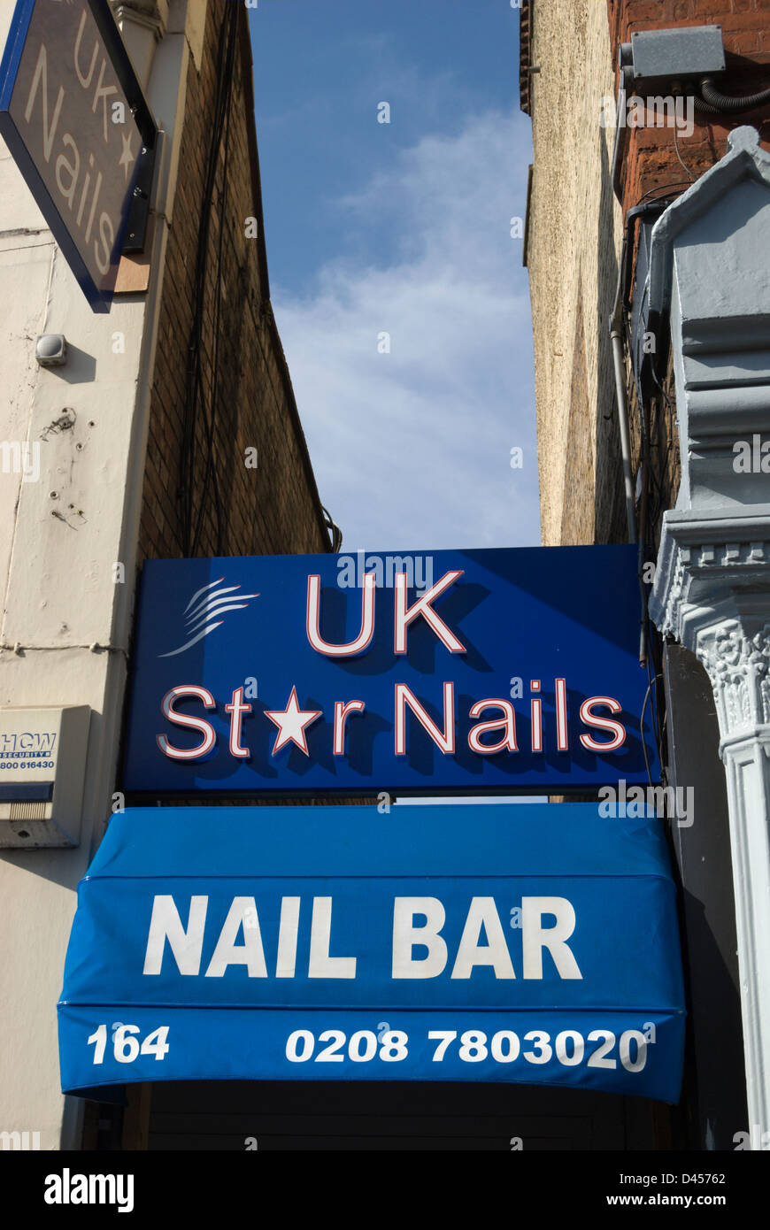 Sign And Awning For A Nail Bar Or Manicuirsts Squeezed Into Gap Between