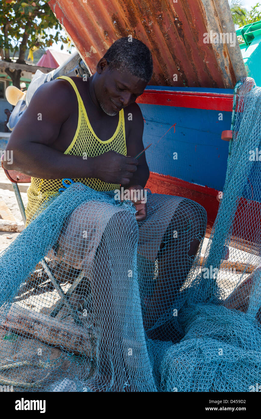Local fisherman mending his fishing nets, Canaries, St Lucia - Stock Image