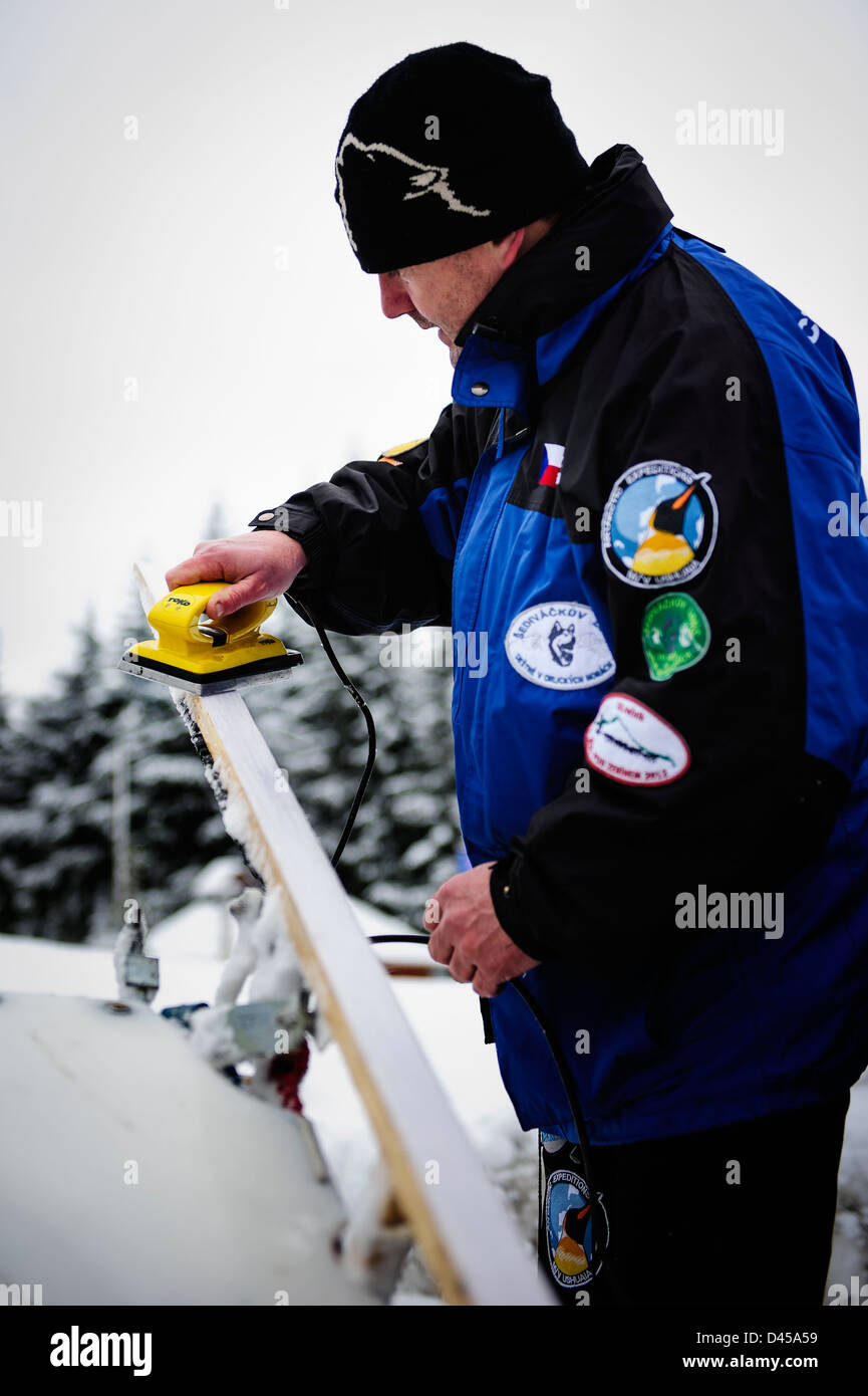 A musher putting wax in his sled before racing, Jakuszyce, Poland. - Stock Image