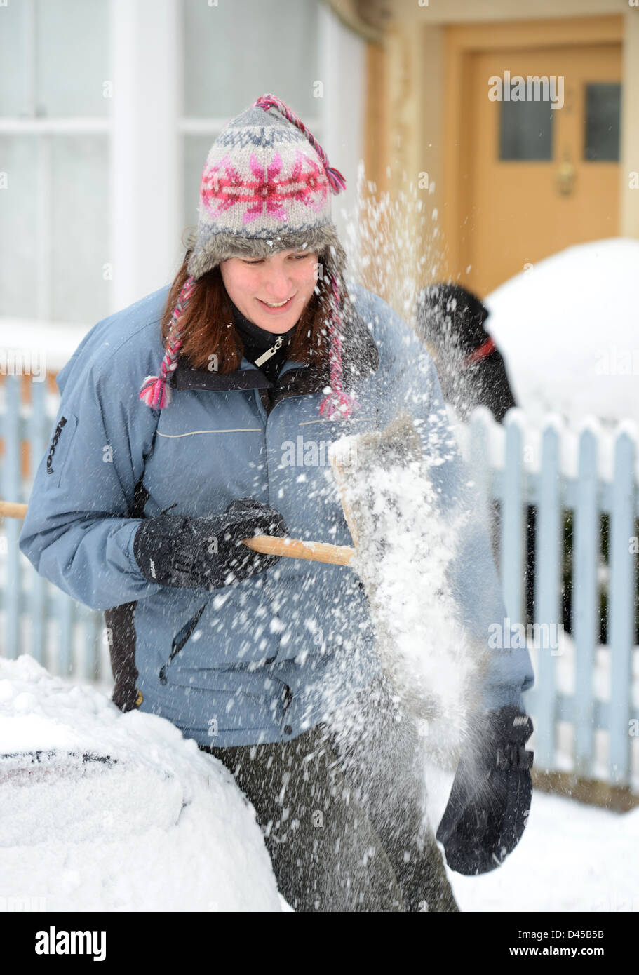A motorist cleans her broom while clearing snow from her car in the village of Badminton Gloucestershire UK - Stock Image
