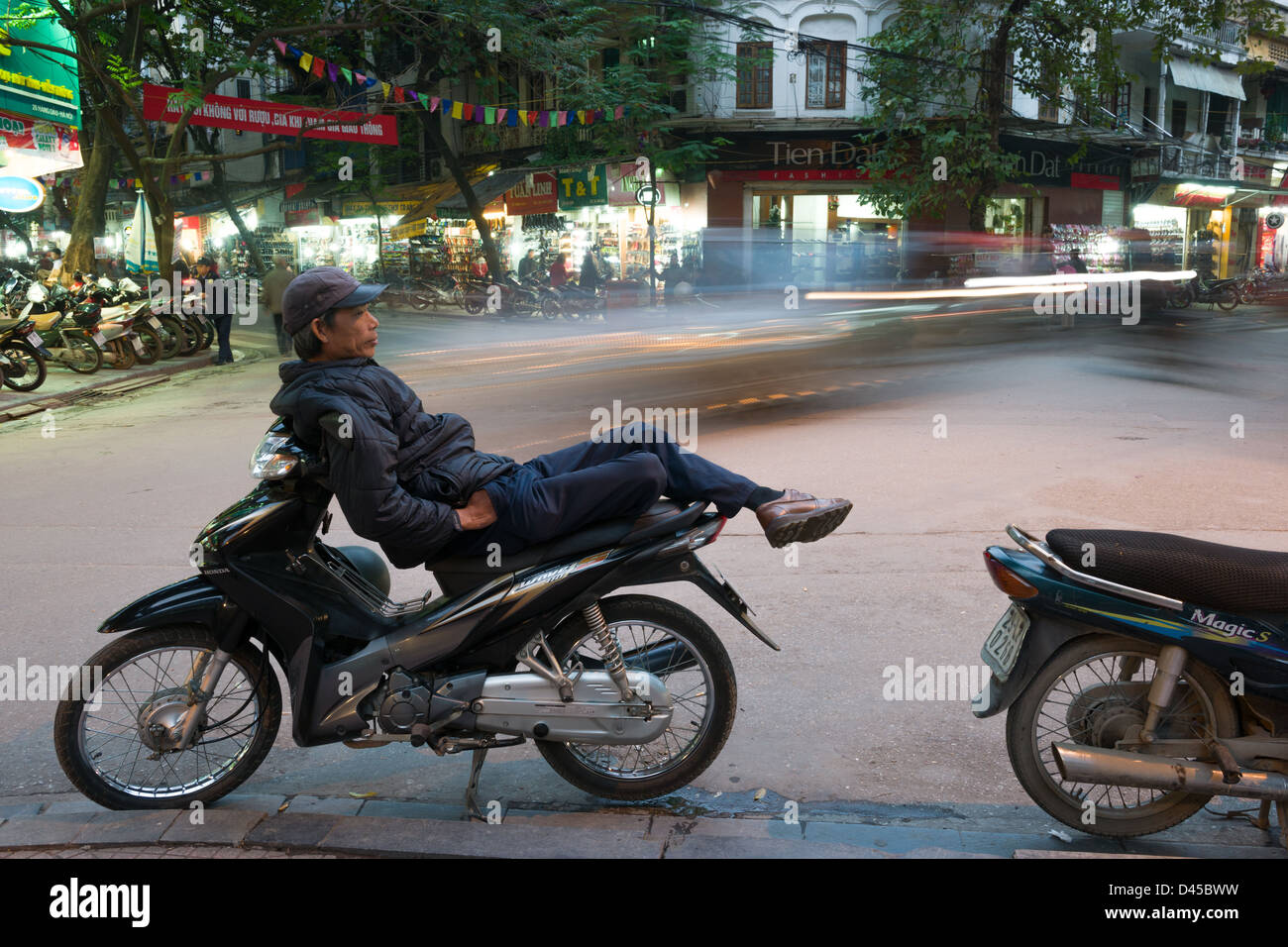 Moto taxi driver relaxing on his motorbike as traffic passes on Lo Su, in the Old Quarter of Hanoi, Vietnam - Stock Image