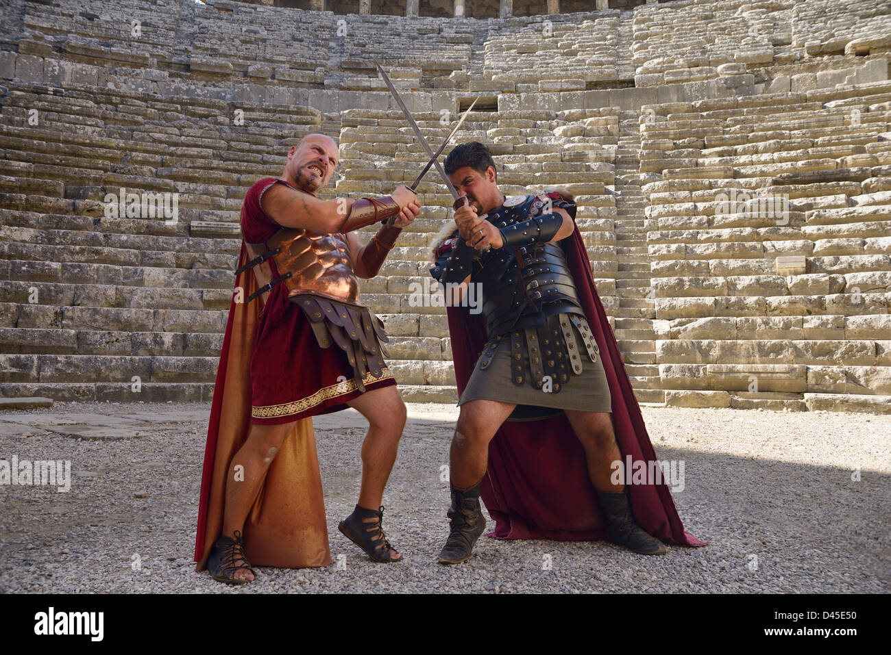 Roman Gladiators sword fighting on the stage at Aspendos theatre Turkey - Stock Image