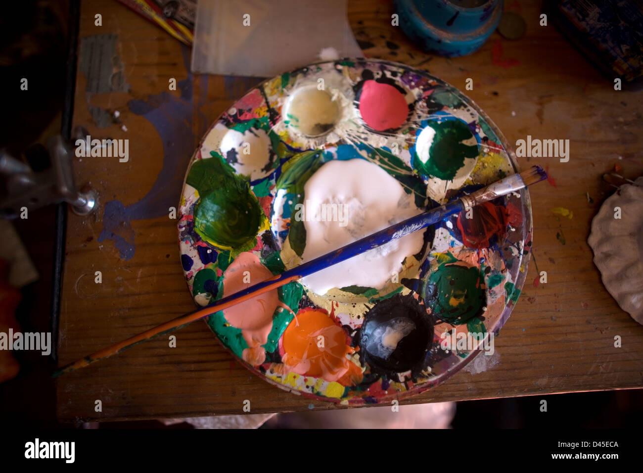 Paint palette and brush in a Mexican folk-art workshop. - Stock Image