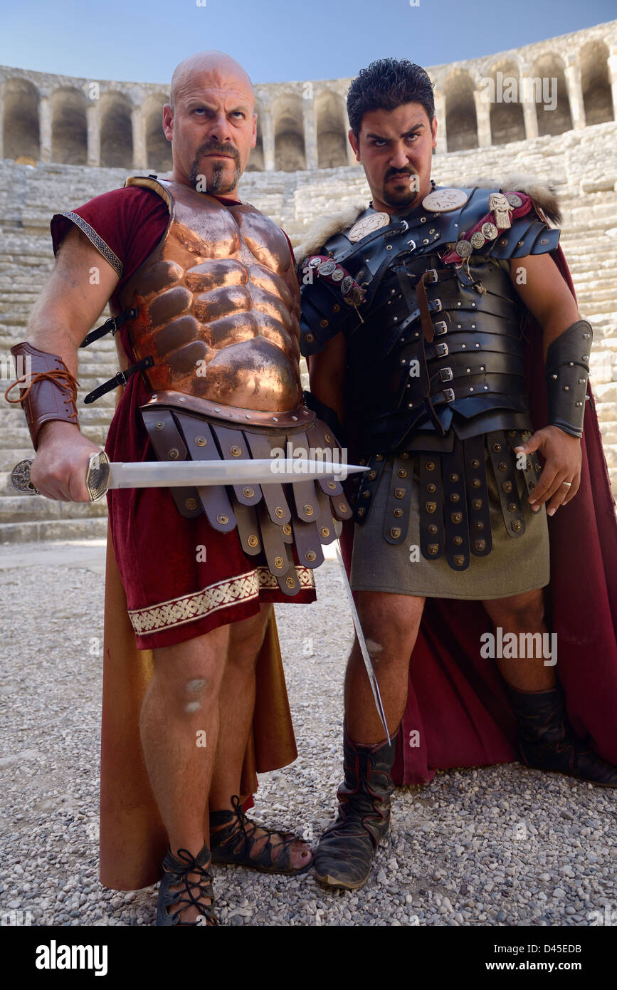 Roman Gladiators scowling before sword fight on stage at Aspendos theatre Turkey - Stock Image