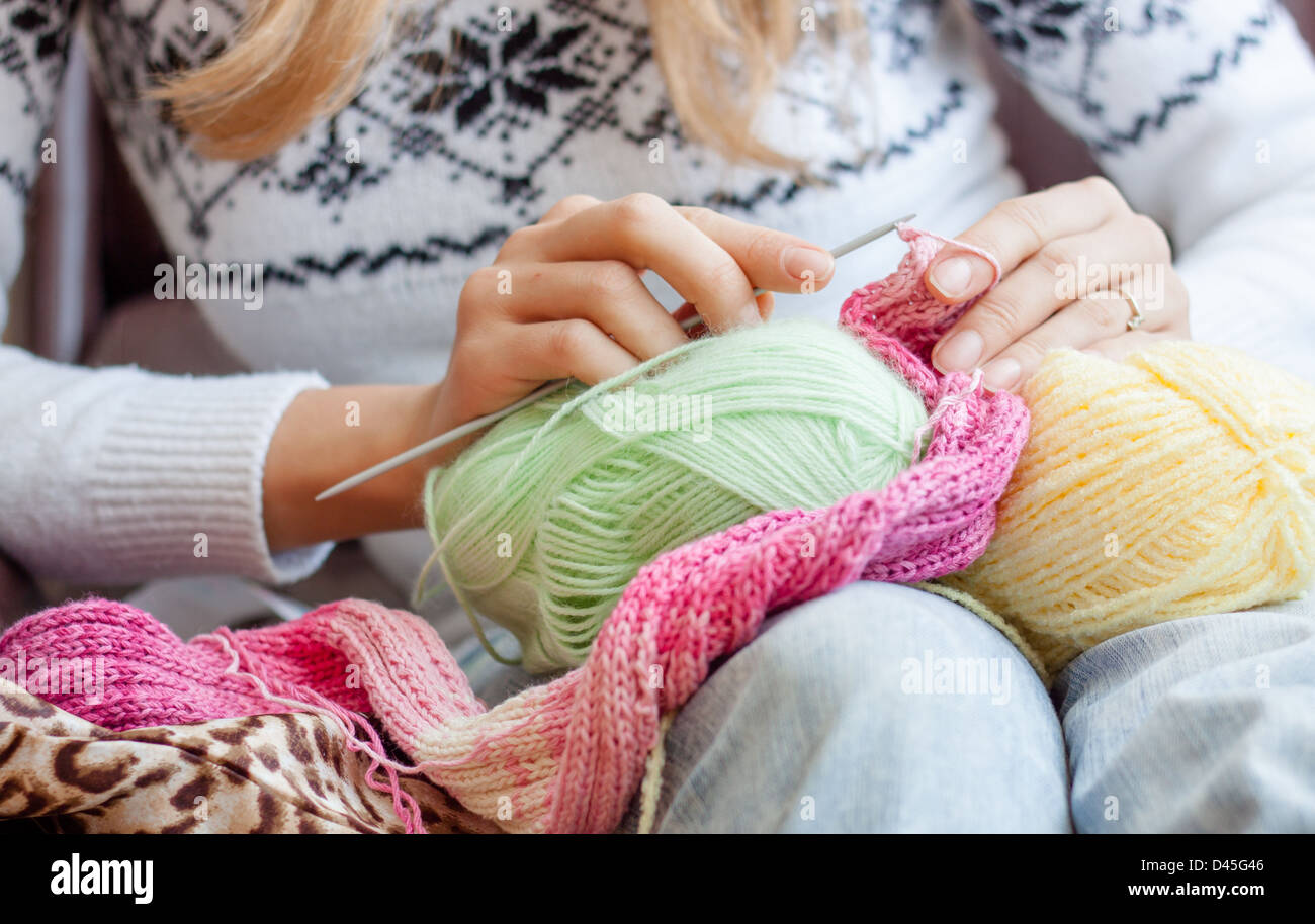 knitting woman , colorful, skein,  hobby, craft,  knit, knitting, hands,needles, pink yarn green, yellow, skeins, - Stock Image