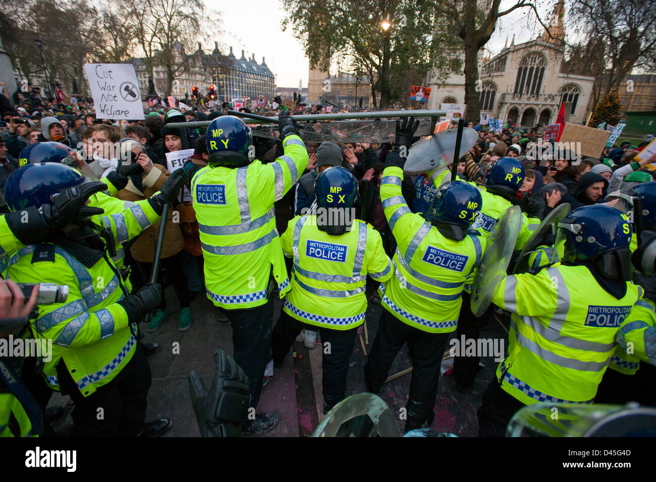 Protesting students attacking a thin line of police in full riot gear with a crowd control barrier, on Broad Sanctuary - Stock Image