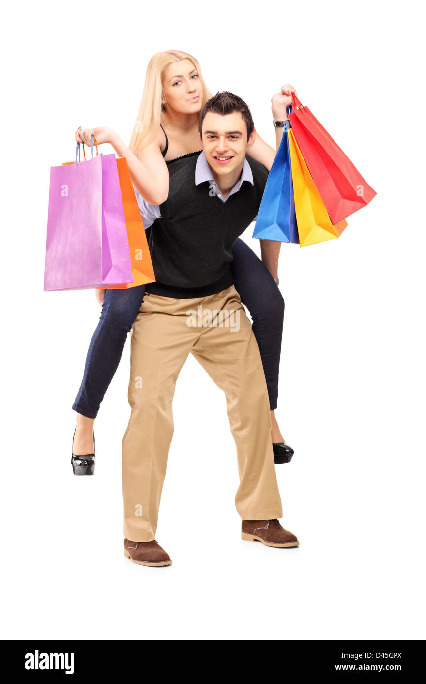 Full length portrait of a young man giving a piggyback ride to a woman with shopping bags isolated on white background Stock Photo