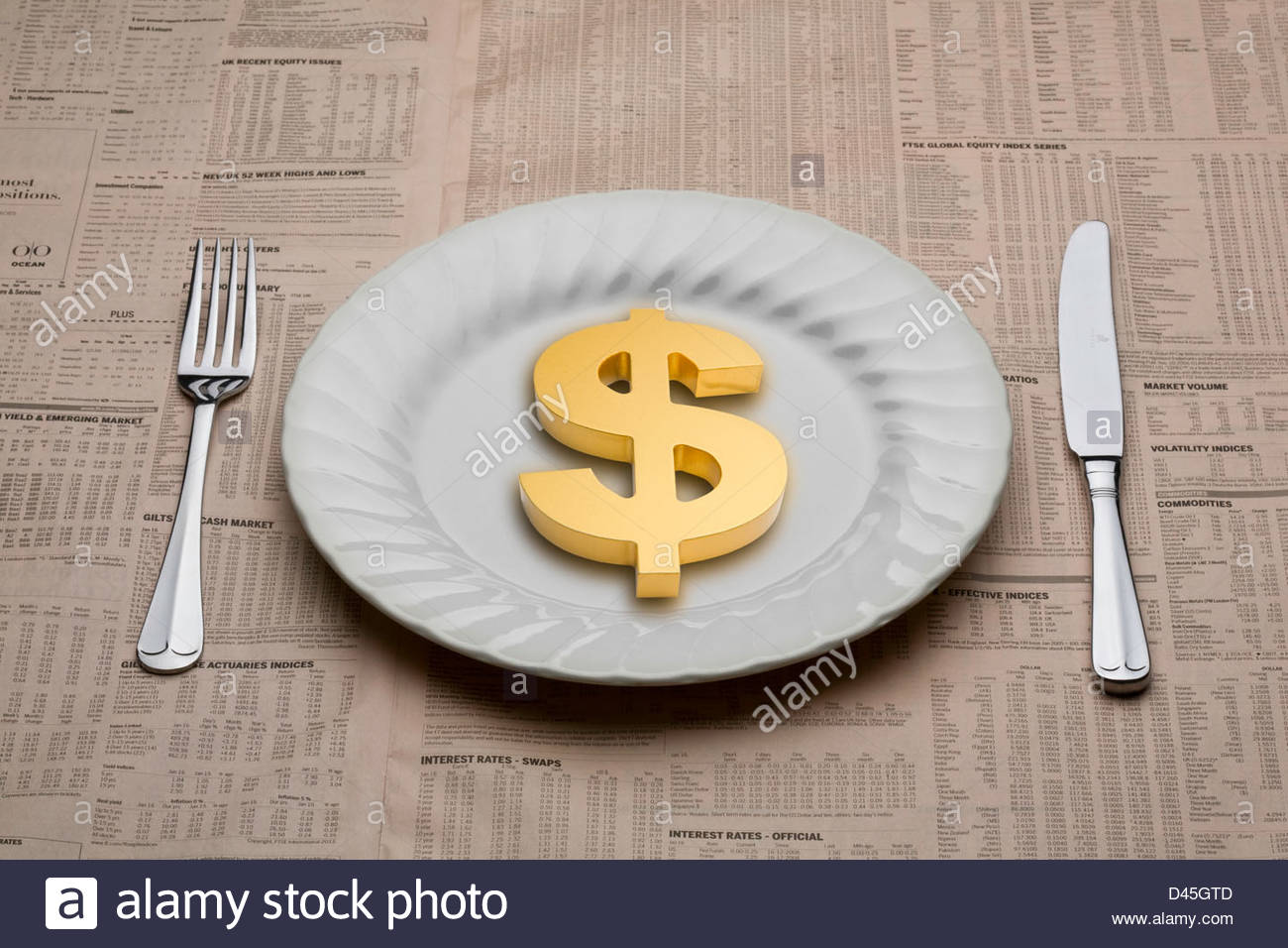 Dollar symbol on a dinner plate with a knife and fork ready to eat for lunch on a table cloth of a financial newspaper - Stock Image