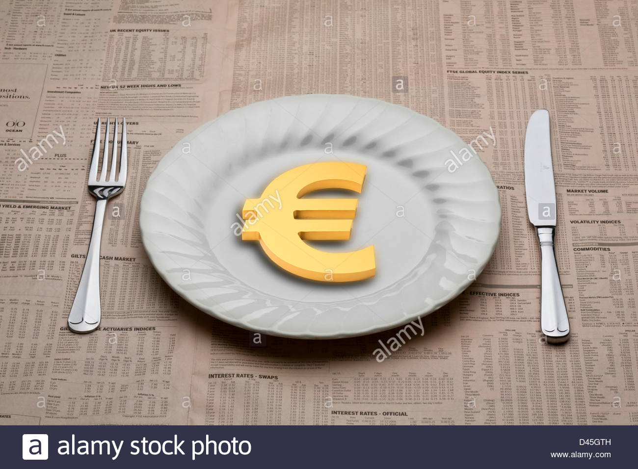 Euro symbol on a dinner plate with a knife and fork ready to eat for lunch on a table cloth of a financial newspaper - Stock Image