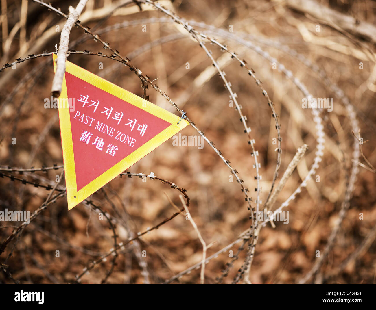 A sign indicating the end of a land mine zone in South Korea, a poignant reminder of the unresolved conflict between - Stock Image