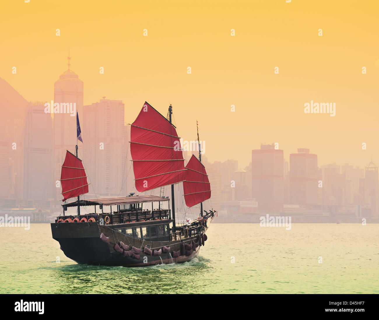 A traditional Junk sailing in Victoria Harbor in Hong Kong. - Stock Image