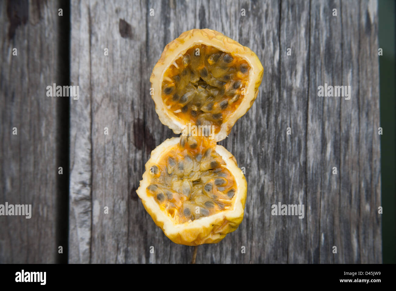 Exotic tropical fruit with yellow rind and black seeds Stock Photo