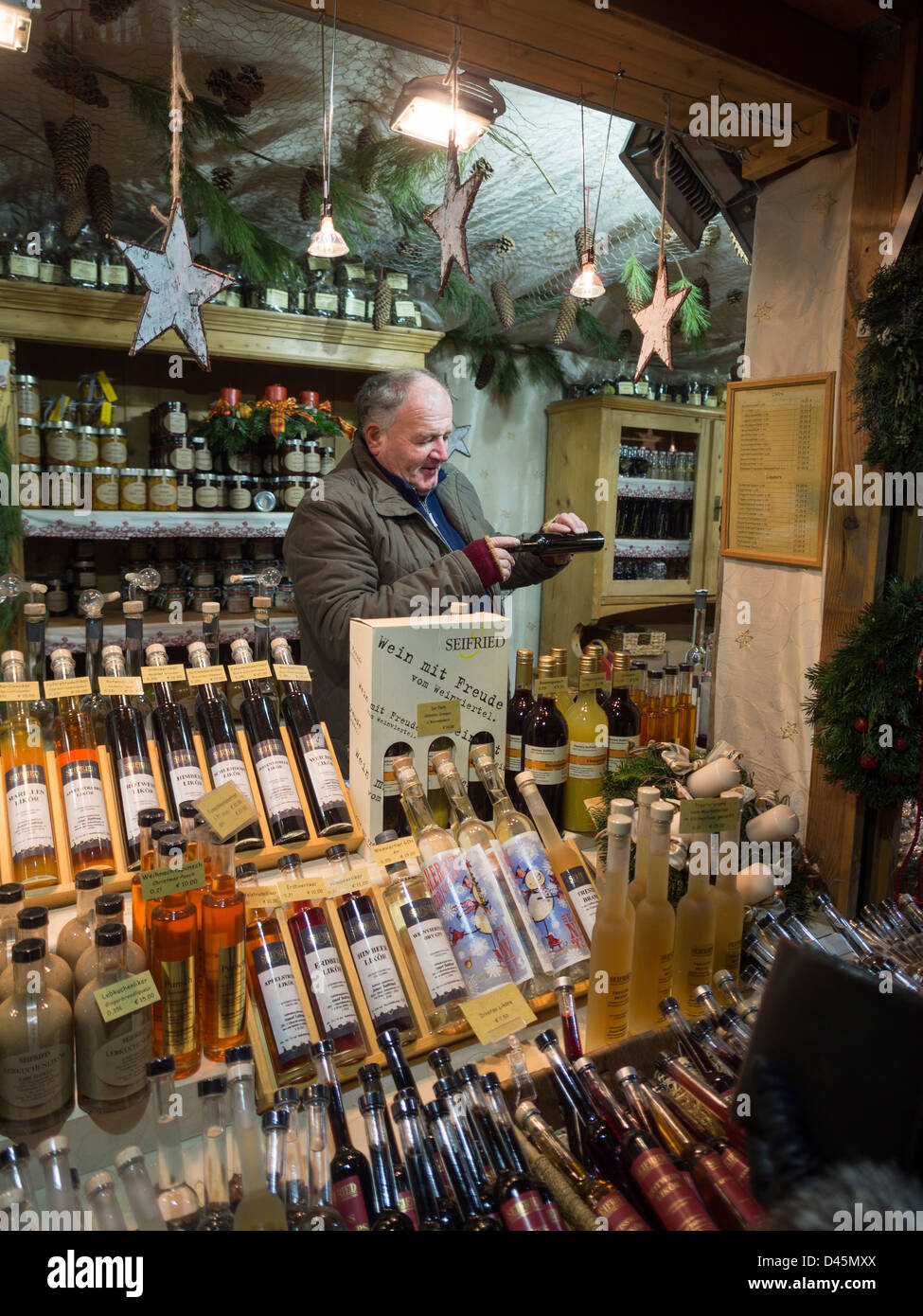 Sampling the Schnapps and other Liqueurs. A shopkeeper at a Christmas Market pours a sample of a liquor - Stock Image