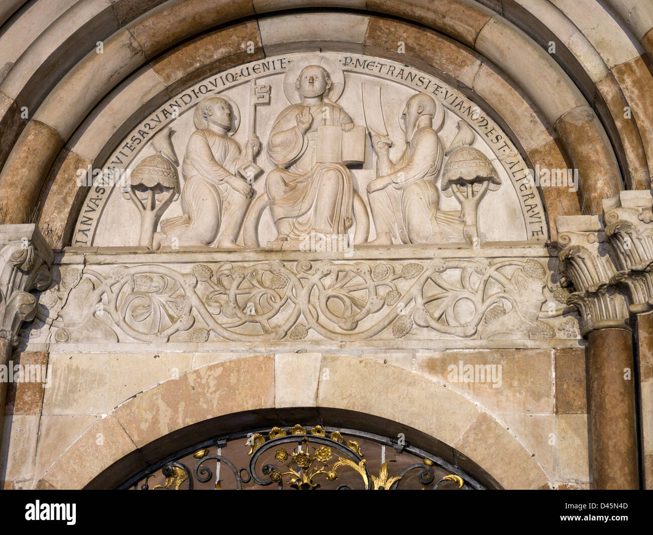 St Peter's tympanum welcome. Above the door a relief showing Jesus with Peter and Paul with a key. - Stock Image