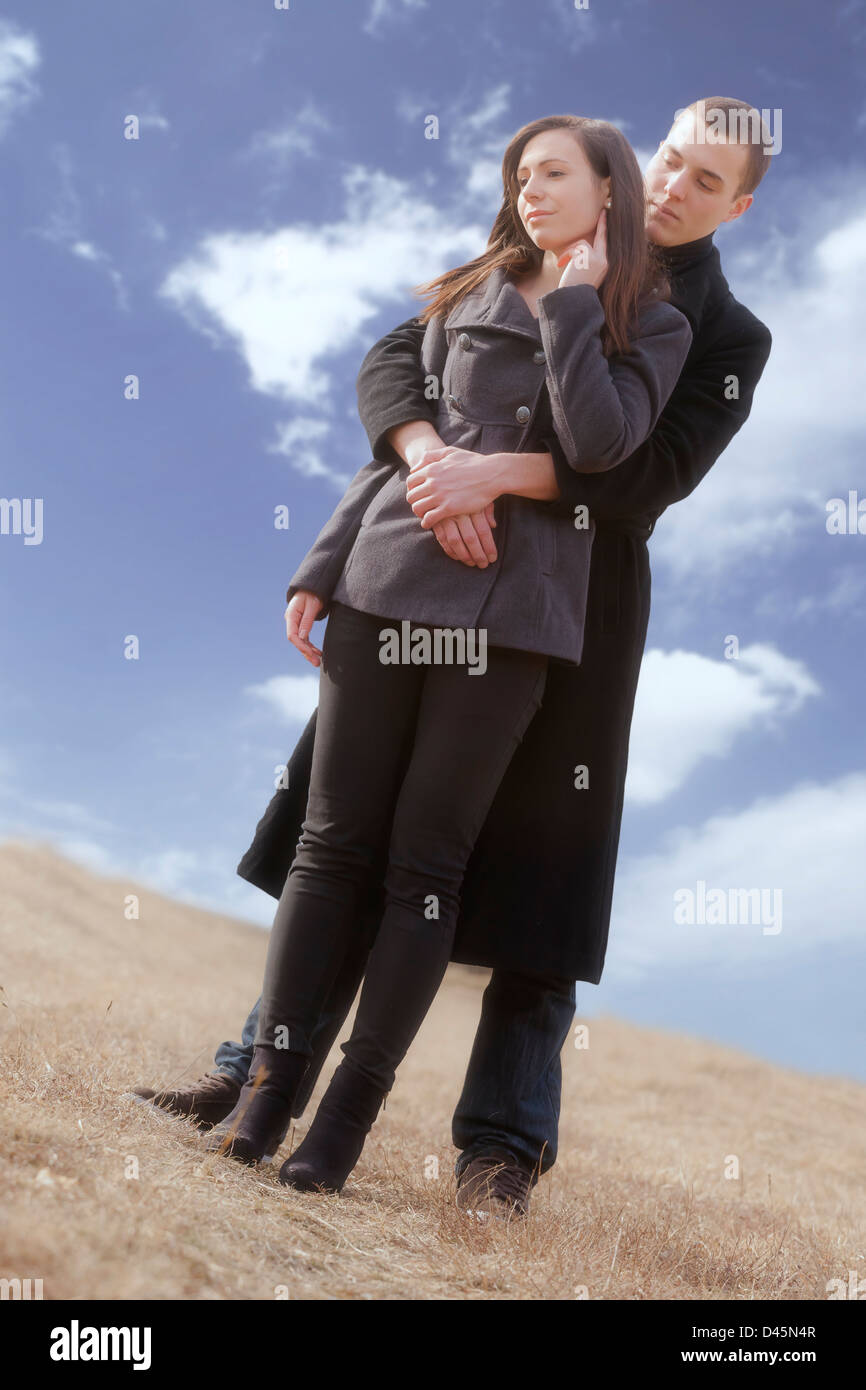 a man hugs his girlfriend in a meadow - Stock Image