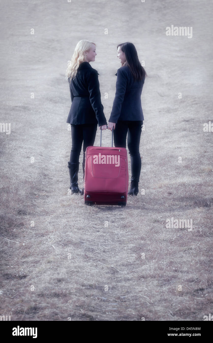 two girlfriends with a red suitcase, laughing - Stock Image
