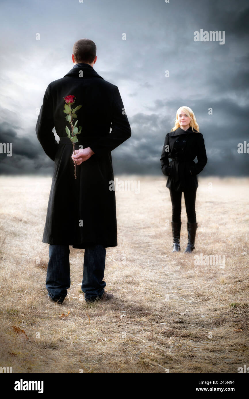 a man hides a red rose to surprise his girlfriend - Stock Image