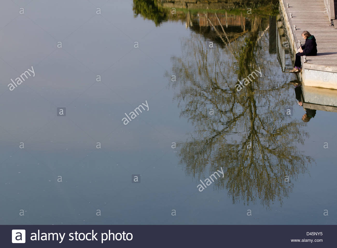 Woman and tree reflected in the quiet flowing water of the river Teifi at Cardigan, Stock Photo