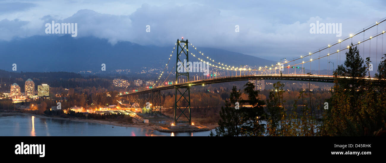 West Vancouver and the Lions Gate Bridge as seen from Stanley Park during dusk, Vancouver, British Columbia, Canada - Stock Image