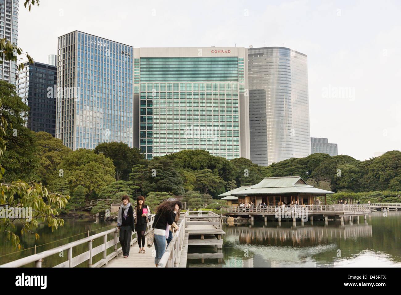 Skyscrapers of Shiodome tower over Nakajima no ochaya teahouse at Hamarikyu Detached Garden, Tokyo, Japan - Stock Image