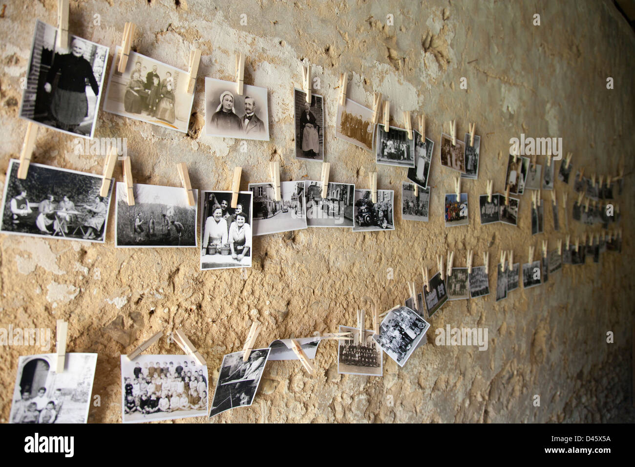 Old black and white family photographs pegged onto string as part of an art installation. - Stock Image