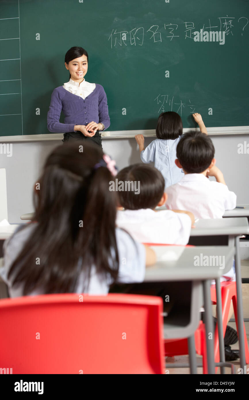 Female Pupil Writing On Blackboard In Chinese School Classroom - Stock Image