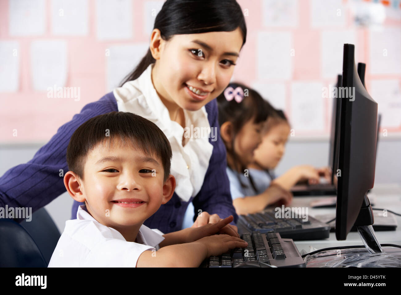 Teacher Helping Student During Computer Class In Chinese School Classroom - Stock Image