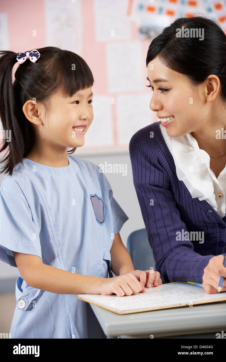 Teacher Helping Student Working At Desk In Chinese School Classroom - Stock Image