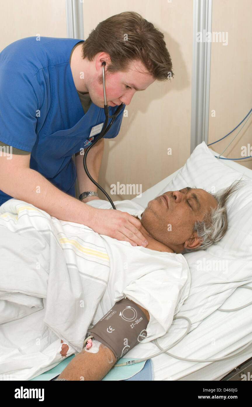 A man resting in a hospital accident and emergency department after being admitted with severe stomach pains. - Stock Image