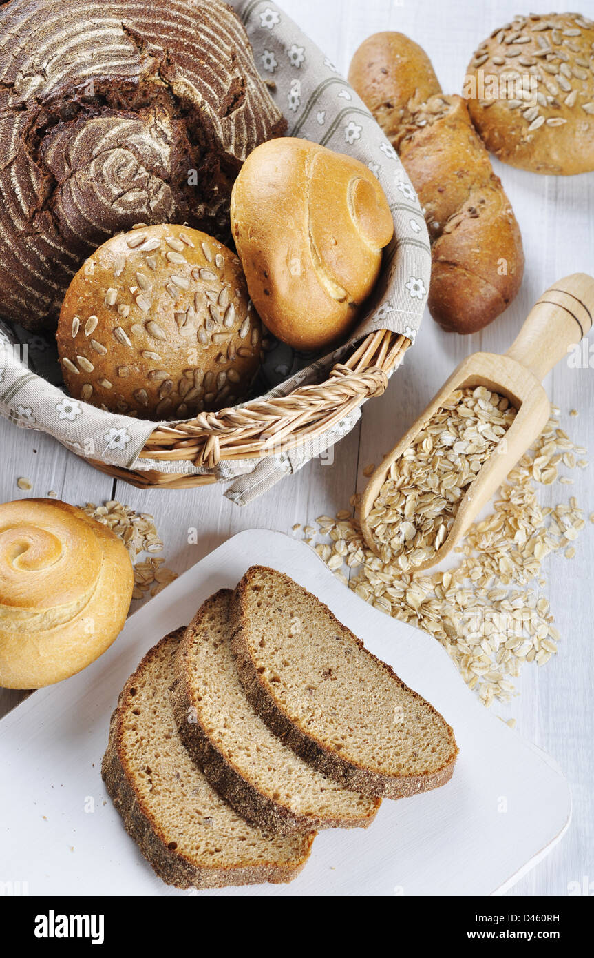 Composition with bread and rolls in wicker basket over white wooden background - Stock Image