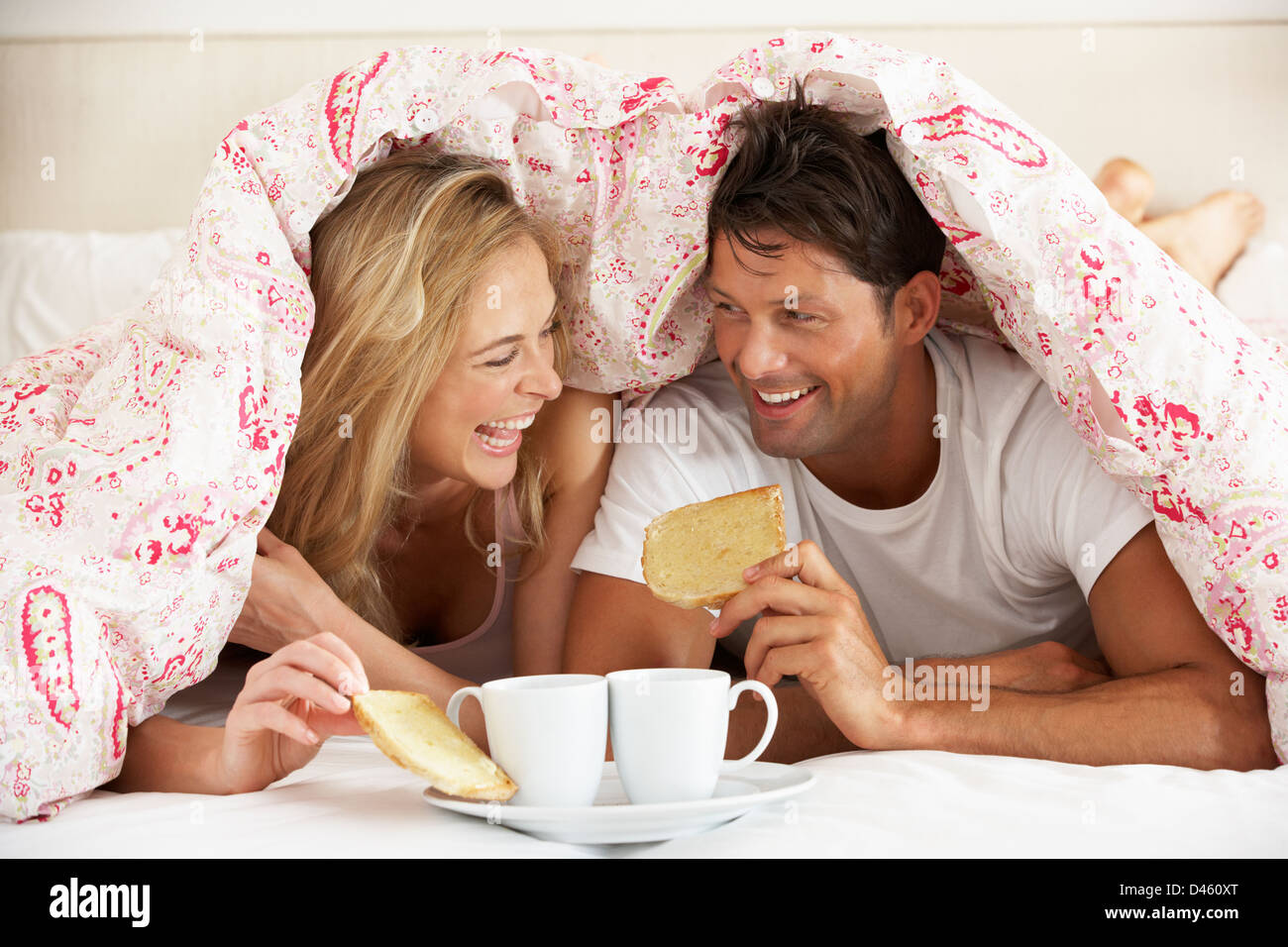 Couple Snuggled Under Duvet Eating Breakfast - Stock Image
