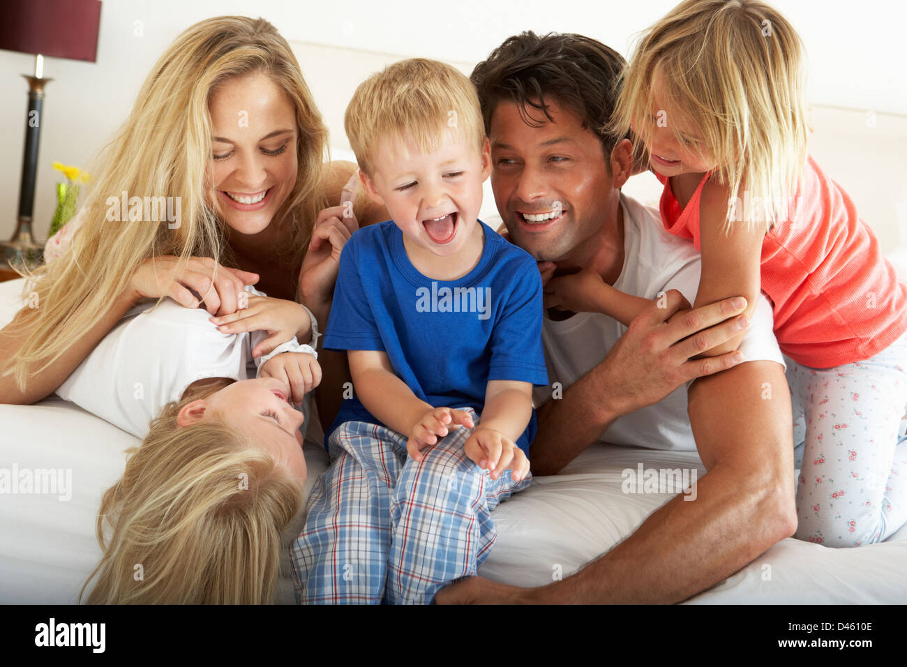 Family Relaxing Together In Bed - Stock Image